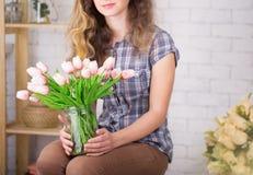 Un adolescente sonríe con los abedules Presentación contra un fondo de la pared de ladrillo con un ramo de tulipanes Fotos de archivo libres de regalías