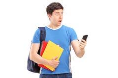 Un adolescente sorprendido que mira un teléfono móvil Fotos de archivo