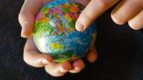 Un adolescente sostiene un mini globo en su mano, con su mano indica la trayectoria de la 'inmigración de África a Europa almacen de video