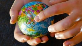 Un adolescente sostiene un mini globo en su mano, con su mano señalando a África, cantidad conveniente para decir la migración almacen de video