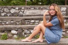 Un adolescente sta sedendosi sui punti di pietra all'aperto Camminata Fotografia Stock