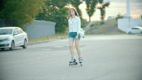 Un adolescente tímido en rollerblades que patina en el camino metrajes