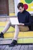 Un adolescente trabaja detrás de un ordenador portátil Fotografía de archivo libre de regalías