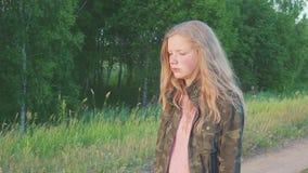 Un adolescente triste soñador en chaqueta militar que camina a lo largo de campo cerca de bosque en la naturaleza El niño tiene p almacen de metraje de vídeo