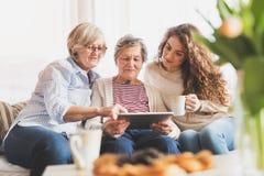 Un adolescente, una madre e una nonna con la compressa a casa Fotografie Stock