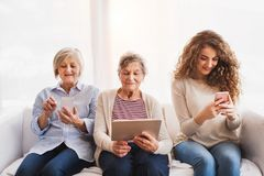 Un adolescente, una madre e una nonna con la compressa a casa Fotografia Stock