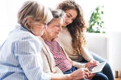 Un adolescente, una madre e una nonna con la compressa a casa Immagini Stock Libere da Diritti