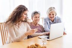 Un adolescente, una madre y una abuela con el ordenador portátil en casa Fotos de archivo