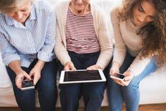 Un adolescente, una madre y una abuela con la tableta en casa Imagen de archivo libre de regalías