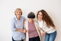 Un adolescente, una madre y una abuela con las gafas de VR en casa Fotografía de archivo