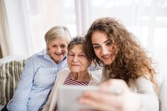 Un adolescente, una madre y una abuela con smartphone en casa Imágenes de archivo libres de regalías