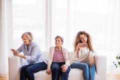 Un adolescente, una madre y una abuela con smartphone en casa Fotografía de archivo libre de regalías