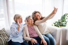 Un adolescente, una madre y una abuela con smartphone en casa Fotografía de archivo