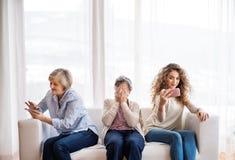 Un adolescente, una madre y una abuela con smartphone en casa Imagenes de archivo