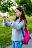 Un adolescente Verano en naturaleza Morenita con las pecas en su cara Hace una foto en la calle Detrás de la parte posterior es u Foto de archivo