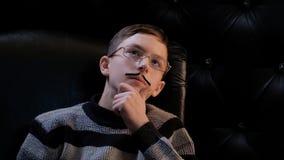 Un adolescente in vetri con la a incollare-sui baffi, portanti un maglione, si siede in una sedia e cerca meditatamente Fondo scu immagini stock libere da diritti