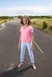 Un adolescente viaja descalzo en un camino vacío Foto de archivo