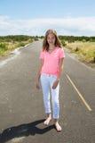 Un adolescente viaja descalzo en un camino vacío Foto de archivo libre de regalías