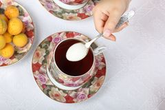 Un adolescente vierte una cucharada de azúcar en té negro Fotos de archivo libres de regalías