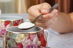 Un adolescente vierte una cucharada de azúcar en té negro Foto de archivo libre de regalías