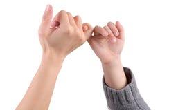 Un adulte et les mains d'un enfant effectuent les sig de promesse Image libre de droits