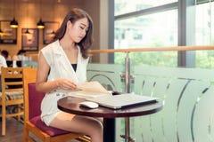 Un adulto joven asiático hermoso está leyendo un libro Fotografía de archivo