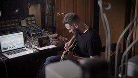 Un adulto que el músico toca la guitarra en su estudio de grabación, él mueve las secuencias de un instrumento musical en un cuar almacen de metraje de vídeo