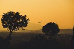 Un aereo e le montagne di basso volo sono profilati al crepuscolo fotografia stock