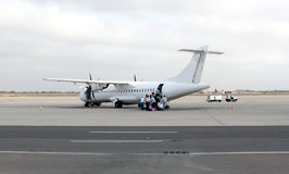 Un aereo e passeggeri sulla pista Fotografia Stock