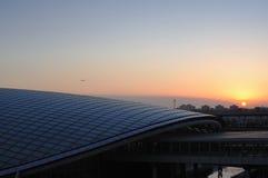 Un aereo sta volando sopra la stazione espressa dell'aeroporto Fotografie Stock Libere da Diritti