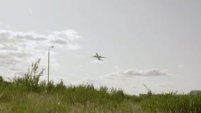 Un aeroplano blanco grande saca del aeródromo cubierto con la hierba verde en el slo-MES almacen de metraje de vídeo