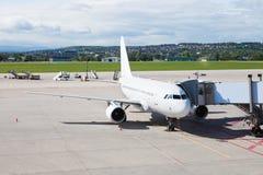 Un aeroplano en el aeropuerto en la pista de despeque Fotografía de archivo libre de regalías