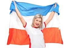 Un aficionado deportivo femenino que sonríe con el indicador de los hollandâs Imagen de archivo