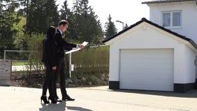 Un agente immobiliare che mostra una pianta della casa del cliente video d archivio