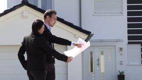 Un agente immobiliare che mostra una pianta della casa del cliente archivi video