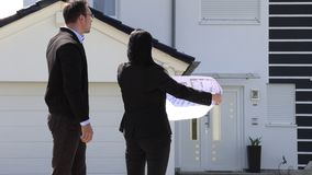 Un agente immobiliare che mostra una pianta della casa del cliente stock footage