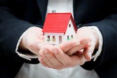 Un agente inmobiliario que sostiene una pequeña nueva casa en sus manos Foto de archivo