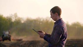 Un agrónomo joven trabaja en el campo, utiliza una tableta En el fondo, el tractor está desenfocado El usar del granjero metrajes