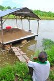 Un agricoltore è triste esaminando la sua azienda agricola del pesce gatto di pangsius nel delta del Mekong del Vietnam Pangasius Fotografia Stock