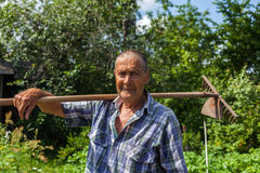 Un agricoltore anziano con un rastrello sulla sua spalla Fotografia Stock