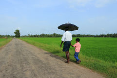 Un agricoltore cammina con un ragazzo l Immagine Stock Libera da Diritti