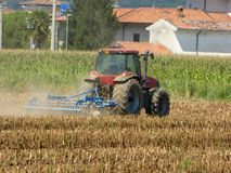 Un agricoltore con un trattore che ara la terra prima della semina nel Lo Immagine Stock