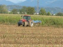 Un agricoltore con un trattore che ara la terra prima della semina nel Lo Fotografia Stock Libera da Diritti