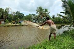 Un agricoltore getta la rete da pesca Fotografie Stock