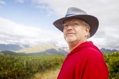Un agricoltore nel rosso guarda fuori da una vigna verde dietro lui Fotografie Stock