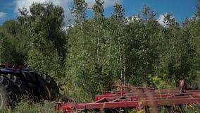 Un agricoltore prepara la terra per la semina dei semi in trattore con l'erpice di disco sul campo vicino ad una foresta della be archivi video