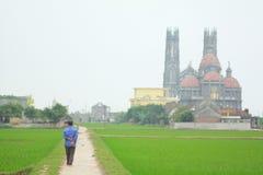 Un agricoltore sta camminando verso una chiesa cattolica in una campagna nel Nord del Vietnam Immagine Stock Libera da Diritti