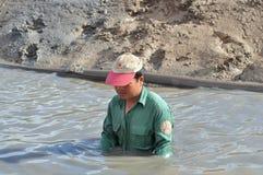 Un agricoltore sta preparando il suo stagno per gamberetto che coltiva nel Vietnam Fotografie Stock