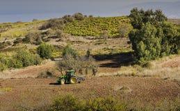 Un agricoltore sul trattore nel suo campo nel Cipro Immagini Stock