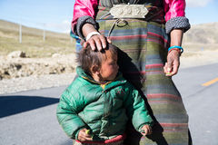 Un agricoltore tibetano con il suo bambino fotografia stock